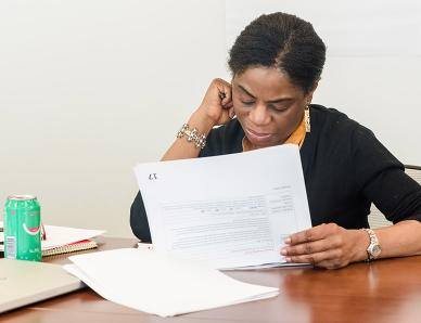 woman at desk looking through paperwork