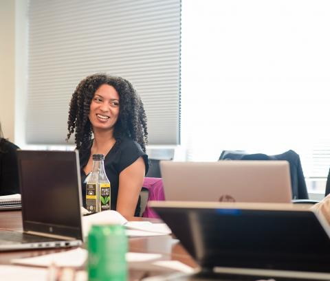 Woman sitting in a meeting smiling and listening