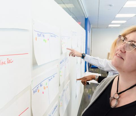 A woman standing at a white board reviewing work