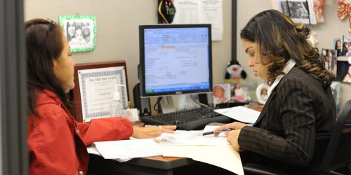Worker assisting another woman fill out paperwork
